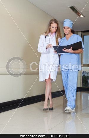 Doctor and nurse with file stock photo, Doctor and nurse reading file while walking in hospital by Tyler Olson