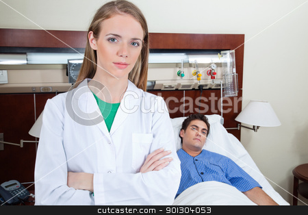 Young female doctor stock photo, Young female doctor in hospital with patient lying on bed in background by Tyler Olson