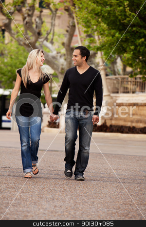 City Walk Couple stock photo, A happy couple walking in the city looking at each other by Tyler Olson