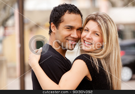 Hug Happy Couple stock photo, A happy couple hugging and looking at the camera by Tyler Olson
