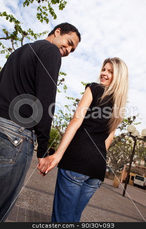 Happy European Couple stock photo, A happy couple walking in the city looking behind at the camera by Tyler Olson