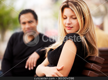 Shy Attractive Woman stock photo, A man and woman sitting on a bench, the woman looking sky by Tyler Olson