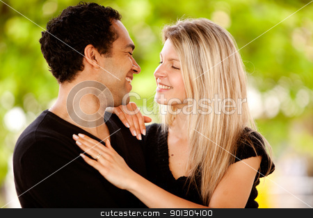 Happy Couple Park stock photo, A happy couple smiling and looking at each other in a park by Tyler Olson