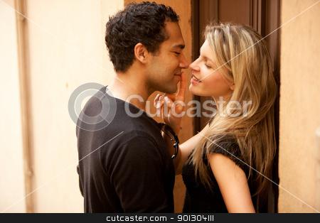 Flirt Couple Kiss stock photo, A couple flirting in an outdoor European urban setting by Tyler Olson