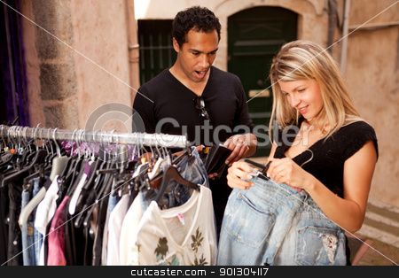 Expensive Clothes Shopping stock photo, A couple shopping, looking at expensive clothes - shallow depth of field, focus on man by Tyler Olson