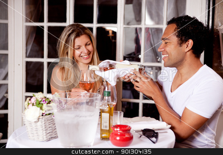Happy Couple in Outdoor Cafe stock photo, A happy couple sharing a bottle of wine in an outdoor cafe in Europe by Tyler Olson
