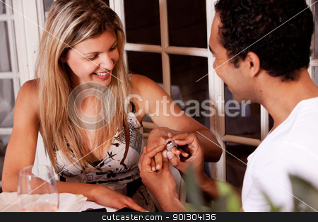Valentine Day Gift stock photo, A man giving a ring present on a date in an outdoor cafe by Tyler Olson
