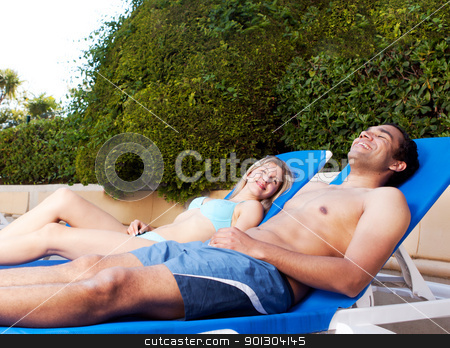 Suntan stock photo, A couple suntanning on beach chairs beside a pool by Tyler Olson