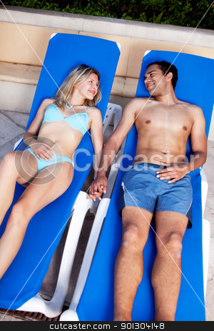 Pool Lounge Chair Couple stock photo, A happy couple lounging in pool chairs by Tyler Olson