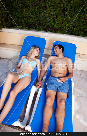 Couple Holiday stock photo, A couple on a holiday sitting by a pool by Tyler Olson