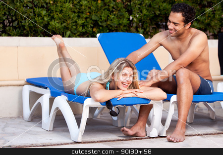 Pool Fun Relax Couple stock photo, A happy couple relaxing beside a pool. by Tyler Olson