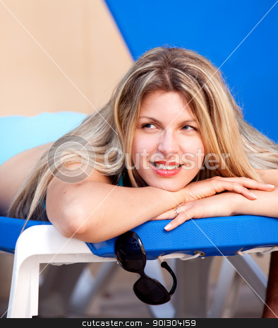 Woman On Beach Chair stock photo, A woman relaxing on a pool side beach chair by Tyler Olson