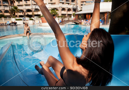 Water Slide stock photo, A brunette woman on an outdoor water slide at a hotel by Tyler Olson