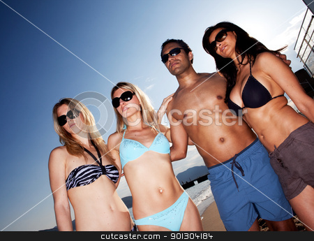 Beach Fashion stock photo, A group of models on the beach against a blue sky by Tyler Olson