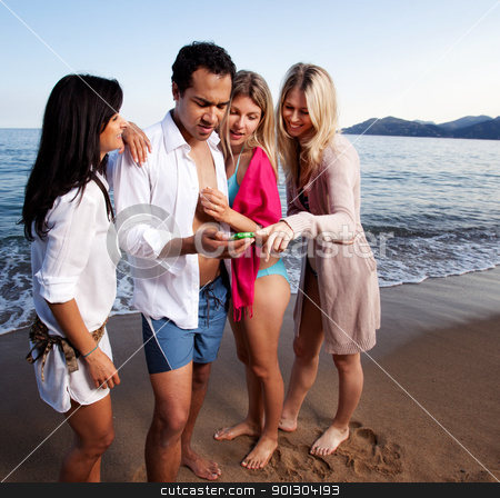 Cellphone Holiday Beach stock photo, A group of friends looking at a cellphone at the beach by Tyler Olson