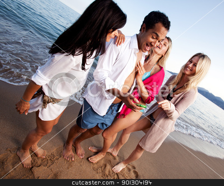 Holiday Friends stock photo, A group of friends having fun at the beach, looking at a cellphone by Tyler Olson