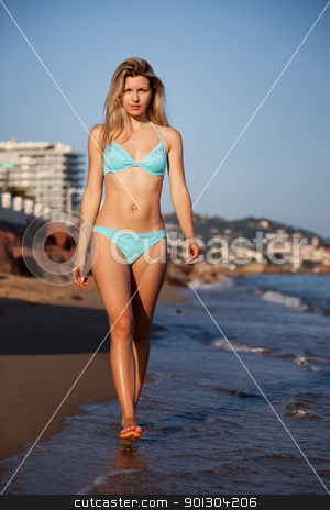 Woman Beach stock photo, A woman walking on the beach looking at the camera by Tyler Olson