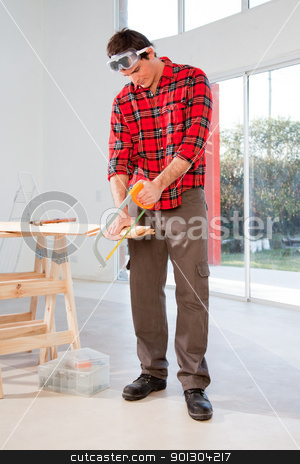 Carpenter stock photo, A carpenter cutting wood with a hand saw in a house by Tyler Olson