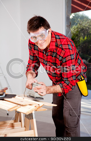 Hand Sander stock photo, A man wearing saftey goggles using an electric hand sander by Tyler Olson