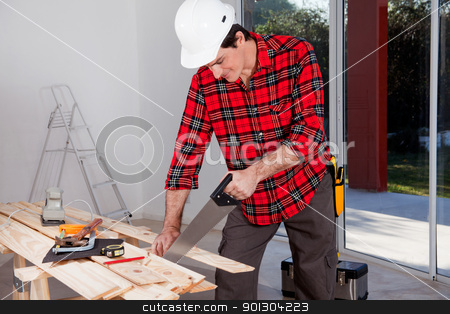 Construction Worker Using Hand Saw stock photo, A construction worker using a hand wood saw while wearing a white safety helmet by Tyler Olson