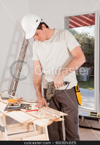 Handy Man Drilling stock photo, A carpenter drilling with a hand drill in a plank of wood by Tyler Olson