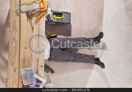 Men working with tools stock photo, Man working under the wooden plank with tools by Tyler Olson