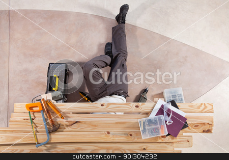 Man working under wooden plank stock photo, Man repairing under the wooden plank with tools by Tyler Olson