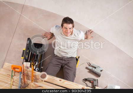 Top view of a happy handsome man stock photo, Top view of a happy handsome man with carpentry tools around by Tyler Olson