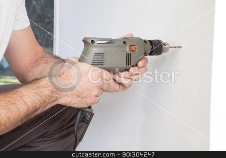 Human hand holding drill machine stock photo, Close-up of human hand holding drilling machine by Tyler Olson