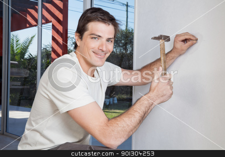 Man hammering the wall stock photo, Portrait of smiling man hammering the wall with nail by Tyler Olson