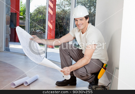 Smiling man with blueprint stock photo, Young man holding blueprint and smiling by Tyler Olson
