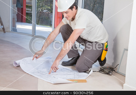 Man pointing at blueprint stock photo, Young man pointing finger at blueprint by Tyler Olson