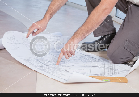 Pointing finger at blueprint stock photo, Close-up of man pointing finger at blueprint by Tyler Olson
