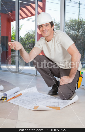Construction worker with blueprint stock photo, Young construction worker pleased with blueprint by Tyler Olson