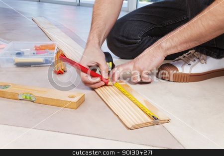 Man marking on plywood stock photo, Man marking on plywood with measuring and pencil by Tyler Olson