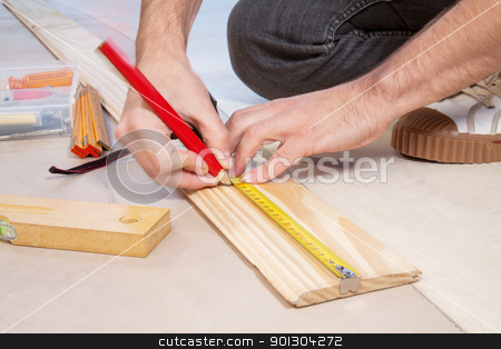 Cropped hand of a carpenter stock photo, Cropped hand of a carpenter taking measurement of a wooden plank by Tyler Olson