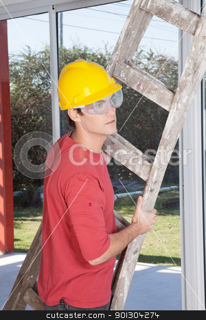 Male construction worker with a ladder stock photo, Male construction worker holding ladder in hand by Tyler Olson