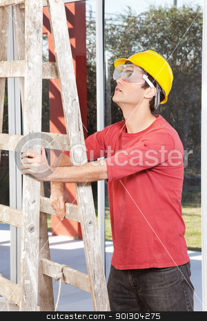 Architect holding ladder stock photo, Architect wearing helmet and eyegear and holding ladder by Tyler Olson