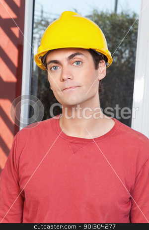 Portrait of young architect stock photo, Close-up portrait of young architect wearing hard hat by Tyler Olson
