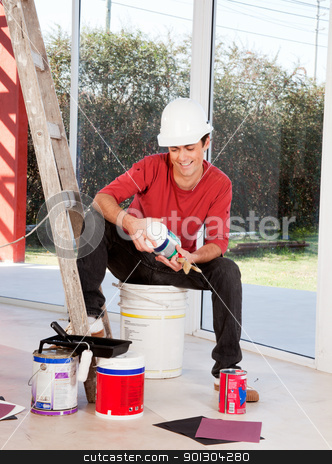 House Painter stock photo, A man with a hard hat, indoors ready to paint by Tyler Olson