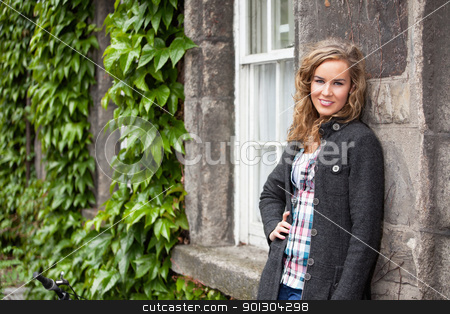 Blond woman leaning against stone wall stock photo, Confident young blond woman smiling an leaning against stone wall by Tyler Olson