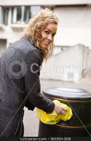 Happy woman putting plastic waste in garbage bin stock photo, Portrait of smiling young woman putting plastic waste in garbage bin by street by Tyler Olson
