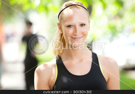 Close-up of an attractive woman smiling stock photo, Close-up of a pretty woman in sports wear with friend in the background by Tyler Olson