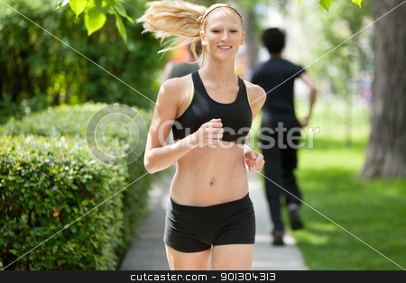 Portrait of a woman jogging stock photo, Beautiful woman running in park with people in the background by Tyler Olson