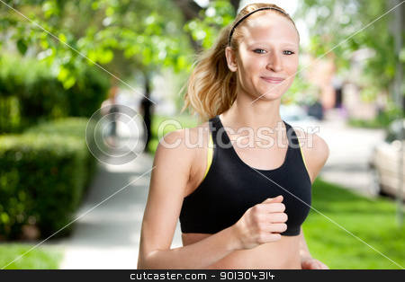 Beautiful woman jogging stock photo, Portrait of a young woman smiling and jogging in the park against blur background by Tyler Olson