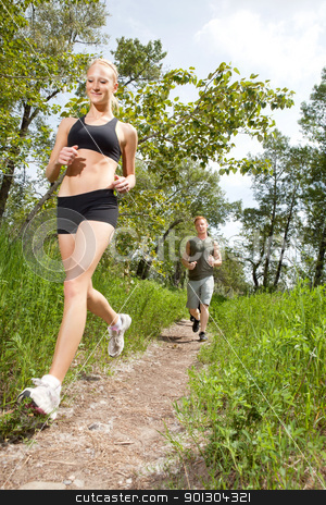 Friends jogging in a forest stock photo, Young man and woman running on a pathway by Tyler Olson