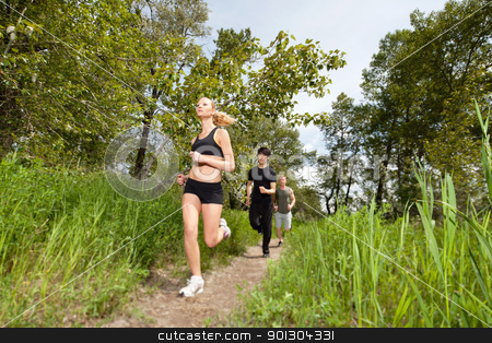 Three people running on pathway stock photo, Health conscious people running on forest trail by Tyler Olson