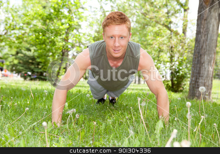 Man doing a push up in park stock photo, Caucasian man doing a push up in park against blur background by Tyler Olson