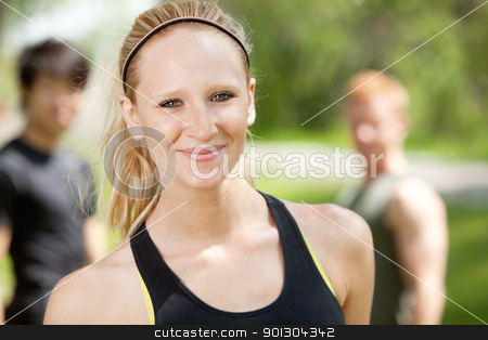 Friends in a park stock photo, Portrait of attractive woman with friends in background by Tyler Olson