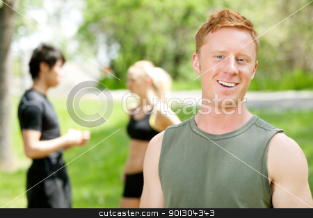 Portrait of a man with friends in the background stock photo, Man smiling and looking at camera while friends talking in the background by Tyler Olson